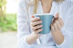 Mulher que guarda a caneca do chá Foto de Stock