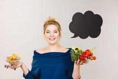 Mulher que guarda a cesta com frutos e o bolo doce fotografia de stock