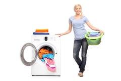 Mulher que guarda a cesta de lavanderia por uma máquina de lavar imagens de stock royalty free