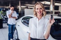 Mulher que guarda chaves do carro novo fotos de stock royalty free