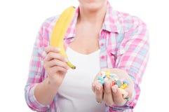 Mulher que guarda comprimidos da banana e da tabuleta Fotos de Stock Royalty Free