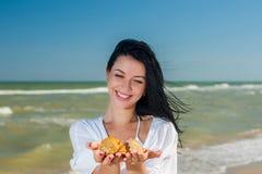 Mulher que guarda conchas do mar Foto de Stock