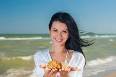 Mulher que guarda conchas do mar Fotografia de Stock Royalty Free