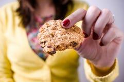 Mulher que guarda a cookie em uma mão Imagens de Stock Royalty Free