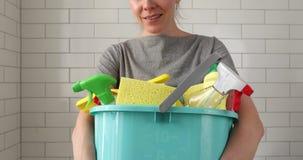 Mulher que guarda a cubeta com produtos de limpeza filme