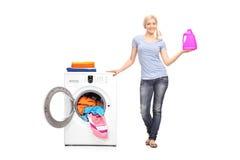 Mulher que guarda detergente ao lado de uma máquina de lavar imagens de stock