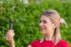 Mulher que guarda DJI Osmo Camera foto de stock