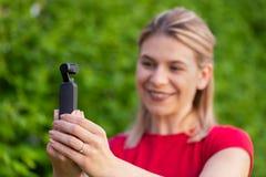 Mulher que guarda DJI Osmo Camera fotografia de stock