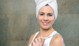 Mulher que guarda a escova de dentes na frente de seu branco imagem de stock