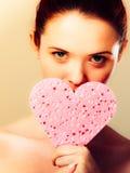 Mulher que guarda a esponja cor-de-rosa do coração nas mãos Fotos de Stock Royalty Free