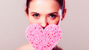 Mulher que guarda a esponja cor-de-rosa do coração nas mãos Fotografia de Stock