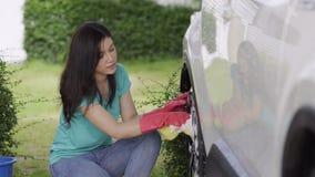 Mulher que guarda a esponja que lava as rodas do carro filme