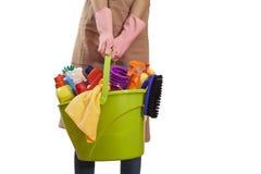 Mulher que guarda fontes de limpeza no fundo branco Foto de Stock