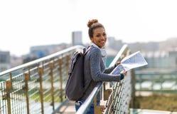 Mulher que guarda fora o mapa e o sorriso Imagens de Stock Royalty Free