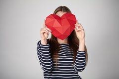 Mulher que guarda a forma de papel poligonal vermelha do coração Imagens de Stock