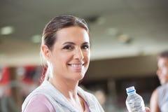 Mulher que guarda a garrafa da água no health club fotos de stock