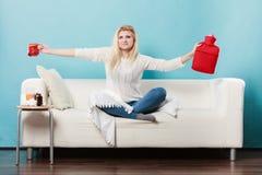 Mulher que guarda a garrafa de água e o chá quentes no copo Imagens de Stock Royalty Free