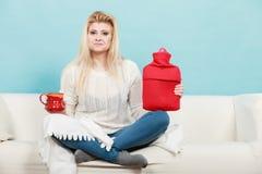 Mulher que guarda a garrafa de água e o chá quentes no copo Imagens de Stock