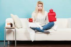 Mulher que guarda a garrafa de água e o chá quentes no copo Fotografia de Stock