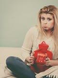 Mulher que guarda a garrafa de água e o chá quentes no copo Fotografia de Stock Royalty Free