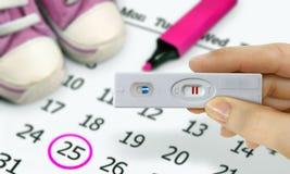 Mulher que guarda jogos do teste com um teste de gravidez positivo Foto de Stock