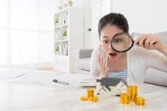 Mulher que guarda a lente de aumento que olha a pilha da moeda de ouro Fotos de Stock Royalty Free