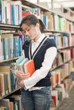 Mulher que guarda livros e que olha forçada Imagem de Stock