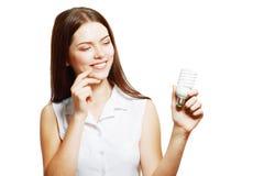 Mulher que guarda a lâmpada de poupança de energia Imagens de Stock