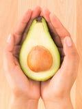 Mulher que guarda a metade do abacate sobre o fundo de madeira com seleto Fotografia de Stock Royalty Free