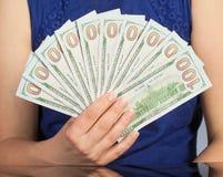 Mulher que guarda 100 notas de dólar novas dos E.U. Imagens de Stock Royalty Free