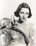 Mulher que guarda o atomizador do perfume fotografia de stock royalty free