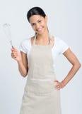 Mulher que guarda o batedor de ovos da cozinha Fotografia de Stock