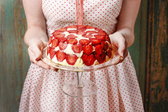 Mulher que guarda o bolo da morango no suporte do bolo Fotos de Stock