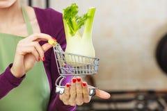 Mulher que guarda o carrinho de compras com erva-doce para dentro Fotos de Stock