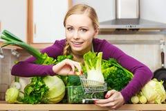 Mulher que guarda o carrinho de compras com erva-doce para dentro Fotos de Stock Royalty Free