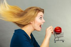 Mulher que guarda o carrinho de compras com maçã para dentro Foto de Stock Royalty Free