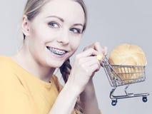Mulher que guarda o carrinho de compras com pão Imagem de Stock Royalty Free