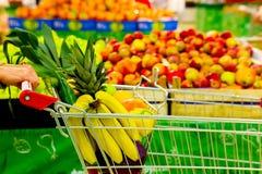 Mulher que guarda o carro com frutas e legumes frescas no centro de compra Foto de Stock