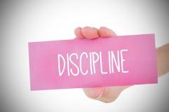 Mulher que guarda o cartão cor-de-rosa que diz a disciplina fotografia de stock royalty free