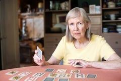 Mulher que guarda o cartão de jogo na tabela fotos de stock