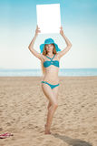 Mulher que guarda o cartaz vazio branco na praia Foto de Stock