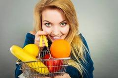 Mulher que guarda o cesto de compras com frutos para dentro fotos de stock