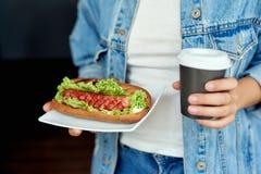 Mulher que guarda o chá ou o café e cachorros quentes deliciosos em um bolo fresco com ketchup e mostarda e alface imagem de stock royalty free
