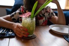 Mulher que guarda o cocktail tropical da cor verde em um vidro de cocktail transparente do estilo do tiki imagens de stock royalty free