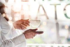 Mulher que guarda o copo de café em um café no fundo do pingo de chuva foto de stock