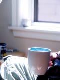 Mulher que guarda o copo de café pela janela Fotografia de Stock Royalty Free