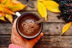 Mulher que guarda o copo do chocolate quente Chocolate quente no tabl de madeira Foto de Stock