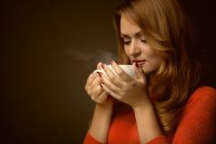 Mulher que guarda o copo quente e os sorrisos fotografia de stock
