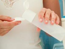 Mulher que guarda o cotonete de algodão e o removedor da composição nas mãos Foto de Stock