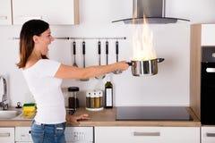 Mulher que guarda o cozimento do potenciômetro com fogo fotografia de stock royalty free